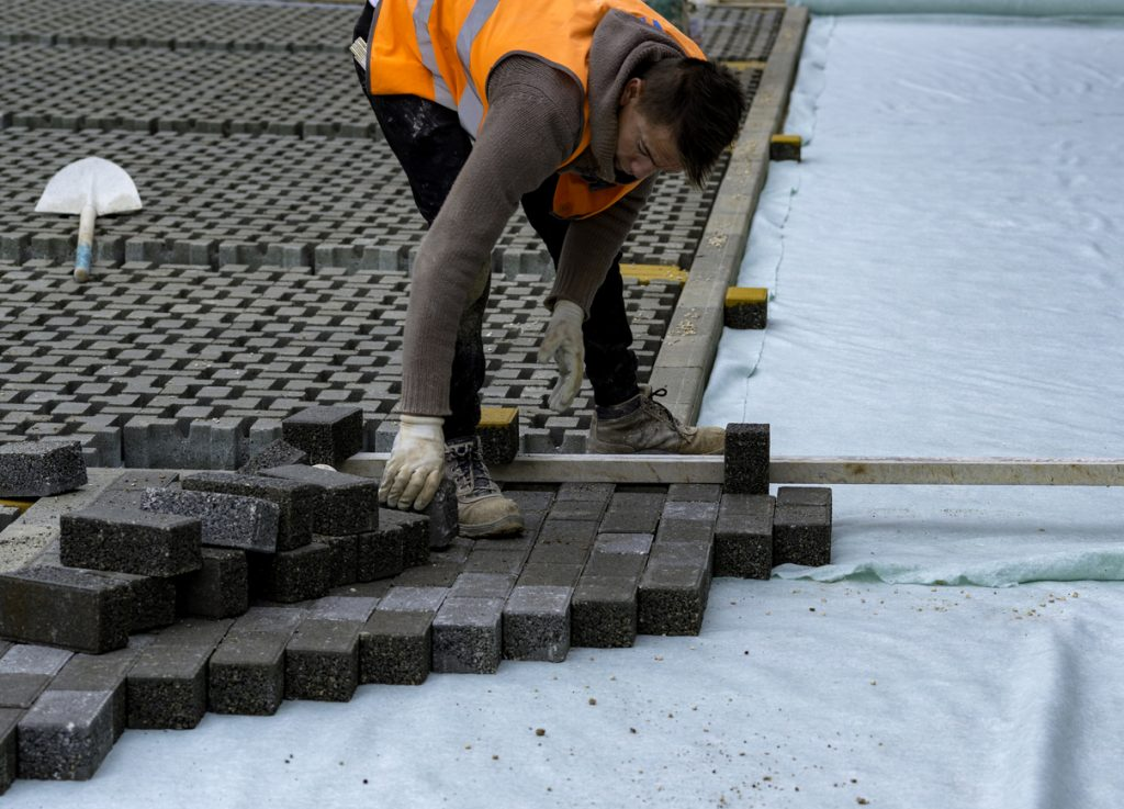 Construction worker laying interlocking paving concrete onto sheet nonwoven bedding sand and fitting them into place